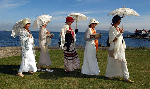 "Five unidentifed women, one of whom reads from ""Ulysses,"" walk along Sandycove in period dress in Dublin, Ireland, Wednesday June 16, 2004, during ""Bloomsday,"" the 100th anniversary commemoration of the day on which James Joyce set the fictional journey of his character Leopold Bloom 100 years ago. (AP Photo/John Cogill)"